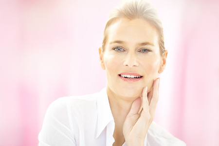 40 year old woman: Caucasian 40 year old woman wearing white formal blouse on pink background and smiling.  NOTE: bokeh haze is originally shot like this with help of props for lightweight spring-like effect. Stock Photo