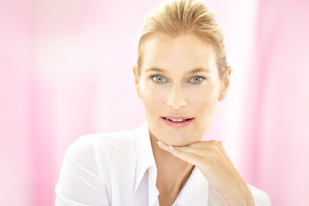 Caucasian 40 year old woman wearing white formal blouse on pink background and smiling. Stock Photo
