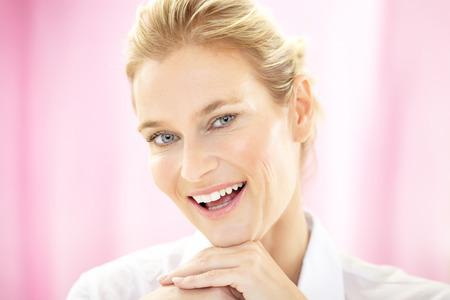 40 year old woman: Caucasian 40 year old woman wearing white formal blouse on pink background and smiling. Stock Photo