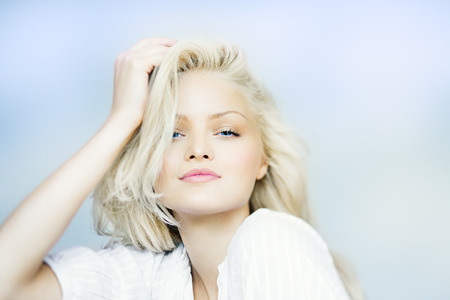 Cheerful looking natural blond woman on light blue background.