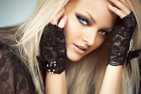 rubia ojos azules: Foto retrato de un modelo de mujer rubia con ojos azules, vistiendo guantes de encaje negro y chaleco.