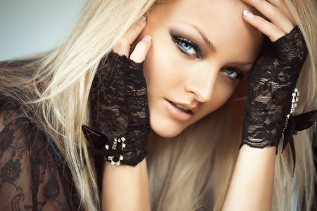 blonde  blue eyes: Stock portrait of a blond woman model with blue eyes wearing black lace gloves and vest.