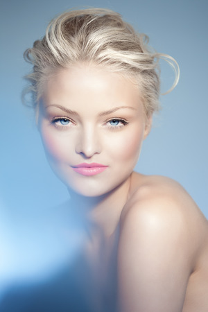 Fashion beauty portrait of a young Caucasian woman over blue background. Blue eyes and blond hair. Glowing skin. Banco de Imagens