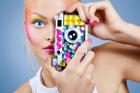 embellished: Model posing with bejeweled vintage photocamera. Focus on eye. Stock Photo