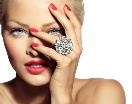 Close-up van een glimlachende model dragen van een grote ring. De meeste nadruk ligt op de hand.