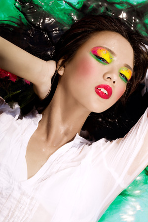 asian hair: Beautiful Asian girl with colorful makeup laying in a pool of green water.