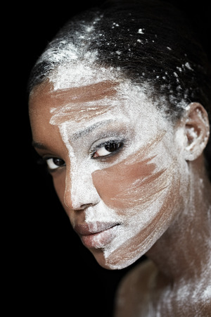 Dark woman with white substance over her face. Slightly tribal look otherwise meant as artistic makeup.