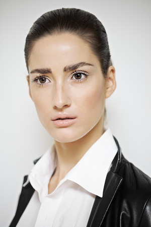 blazer: Portret  series of a fashion model with dark gathered hair wearing white shirt and black leather blazer.