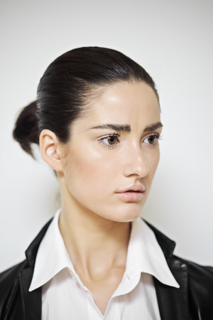 gathered: Portret  series of a fashion model with dark gathered hair wearing white shirt and black leather blazer.
