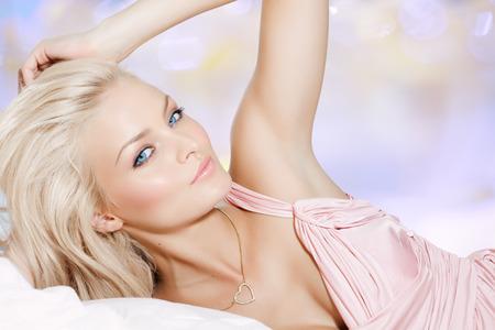 rubia ojos azules: Hermosa mujer rubia que pone en vestido rosa.