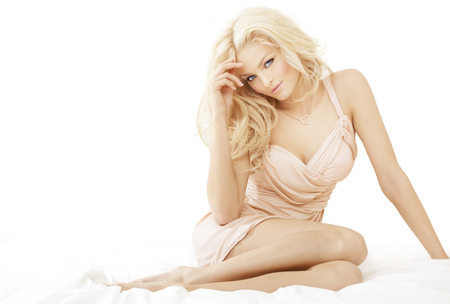 bedsheets: Young blond woman sittiing on bedsheets wearing light colored silk dress.
