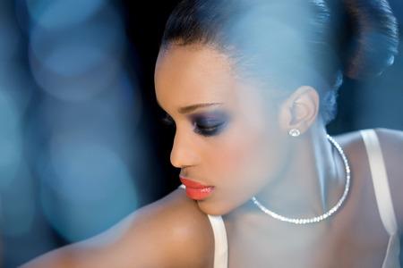 dark skin: Bella sposa con la pelle scura seduti intorno razzi bokeh blu (bokeh originariamente girato come questo). Archivio Fotografico