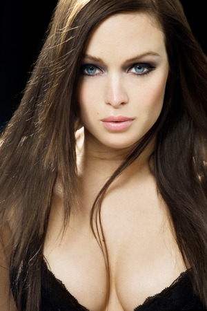 brown hair blue eyes: Beautiful model with blue eyes and long brown hair looking straight into camera. Stock Photo