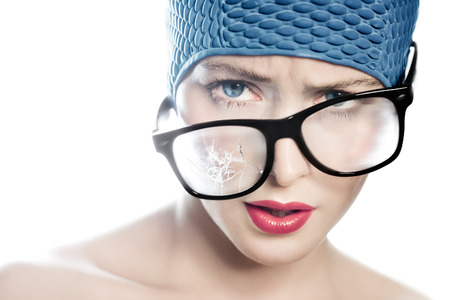 swimming cap: Closeup of a woman wearing large glasses broken on one side and a swimming cap. Stock Photo