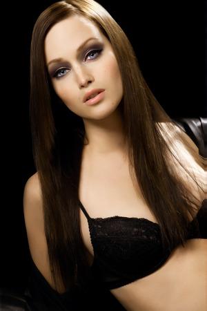 black hair blue eyes: Model with long hair posing in black lingerie.