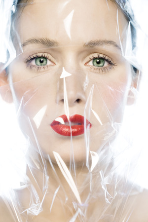 Closeup of a female face wrapped in cellophane.