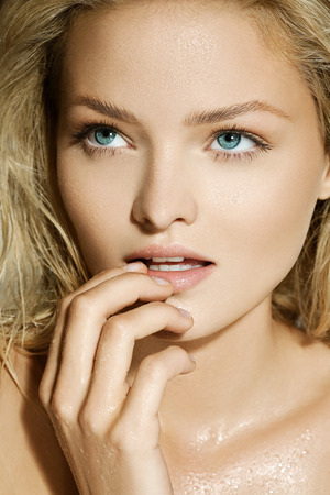 hand water: Blond model with wet face.