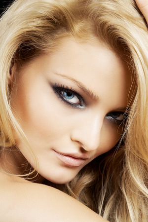 blonde yeux bleus: Portrait d'un beau modèle blond de race blanche aux yeux bleus sur fond noir.