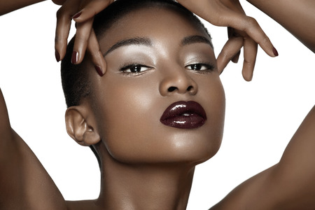 african lady: Beautiful African fashion model closeup. Plum lipstick and dark nail polish. Posing over white background.