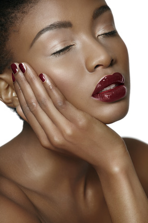 cropped shots: Beautiful serene African woman with dark lipstick and manicure.