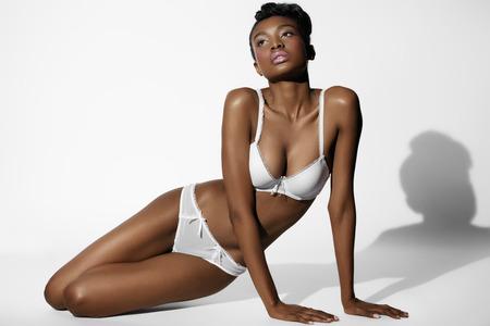 woman underwear: African model posing in white lingerie.