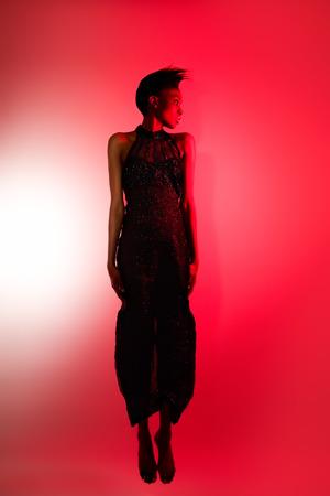 mannequin africain: Mod�le de la mode africaine flottant dans l'air rouge dans une robe � paillettes vintage. Filtre rouge utilis� sur le flash.