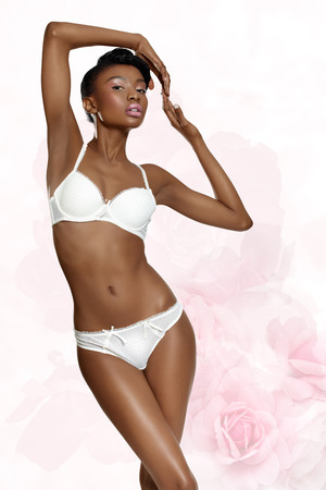 gracious: Very romantic lingerie visual with dark model and light-pink floral background.