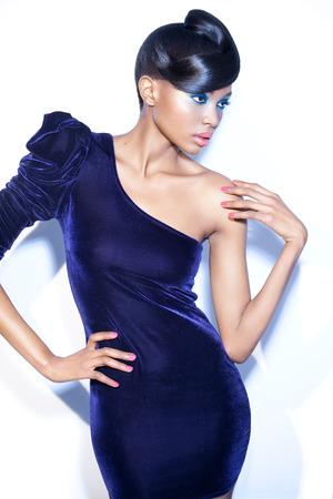 Model poseren in donkere fluwelen one-shoulder jurk.