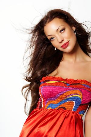 capelli castani: Giovane donna caucasica con lunghi capelli castani posa in studio indossando vestito di seta colorata.