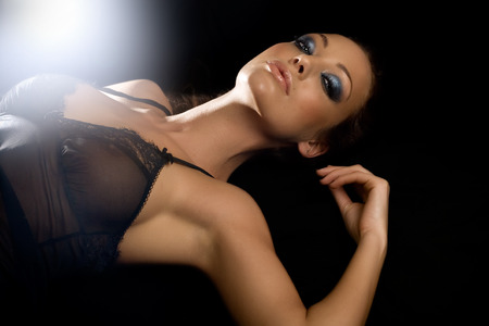 woman laying down: Beautiful woman laying down on black.