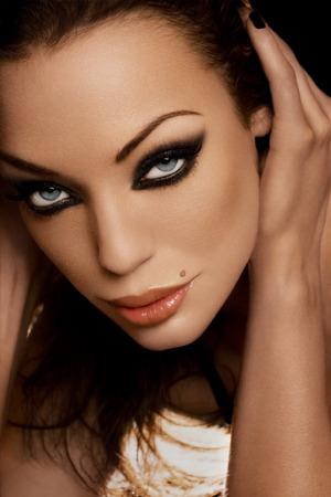 black hair blue eyes: Beautiful glamorous woman resting on her hands.