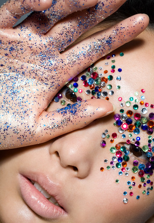 glitter makeup: Fashion model covered in gems. Stock Photo