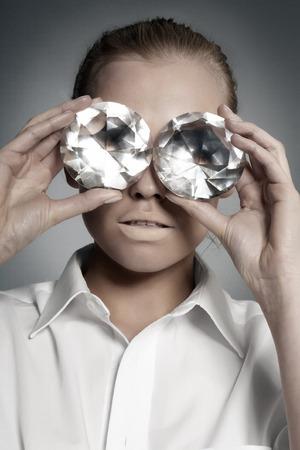fake: Model putting huge diamonds to her eyes.