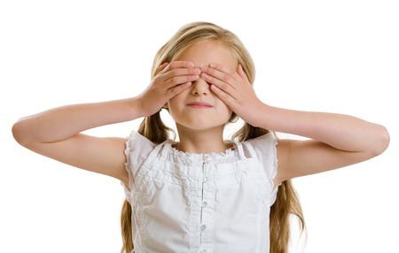 10 years: Smiling 10 years old girl covering her eyes. Stock Photo