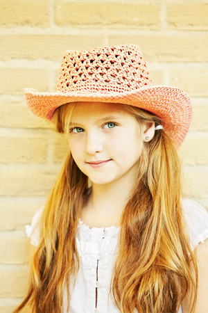 long blonde hair: Ten year old caucasian girl outdoors wearing summer hat.