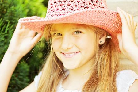 ten year old: Ten year old caucasian girl outdoors wearing summer hat.