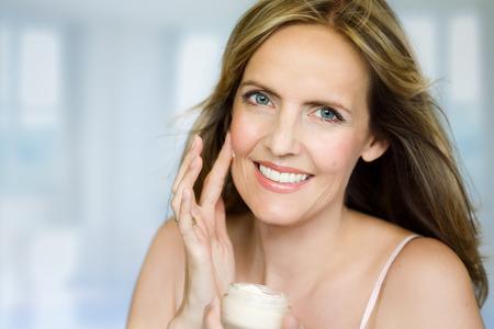 De vrouw is de toepassing van crème op haar gezicht. Stockfoto