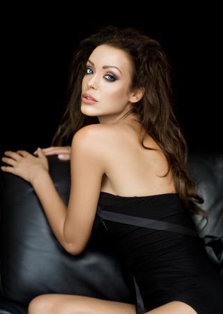 long black hair: Gorgeous model sitting on leather sofa.
