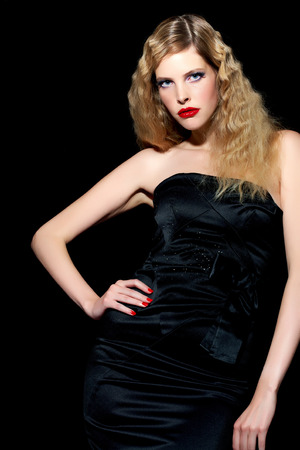 cocktail dress: Model with blond hair wearing black silk cocktail dress on black background. Stock Photo