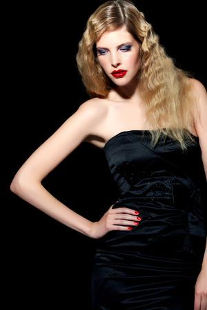 blonde yeux bleus: Modèle aux cheveux blonds porter robe de cocktail en soie noire sur fond noir. Banque d'images