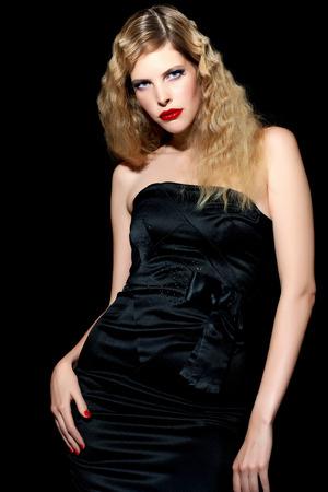 cocktaildress: Model met blond haar het dragen van zwarte zijden cocktail jurk op zwarte achtergrond.