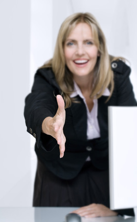 reached: Friendly businesswoman with hand reached out for a handshake. Shallow DOF with focus on hand. Stock Photo