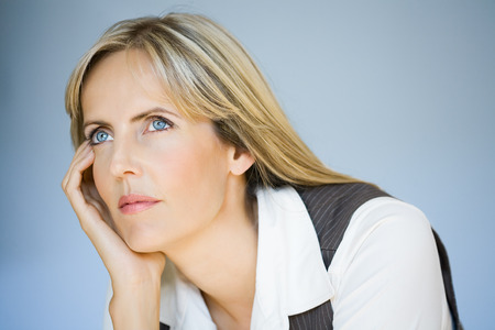 mujer pensativa: Mujer pensativa sobre fondo azul.