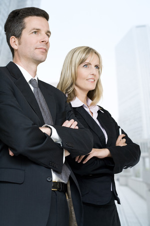 Formally dressed man and woman looking away with arms crossed. Focus on man.