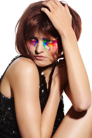 brown hair blue eyes: Fashion model with short dark fluffy hair and colorful make-up with paint effect.