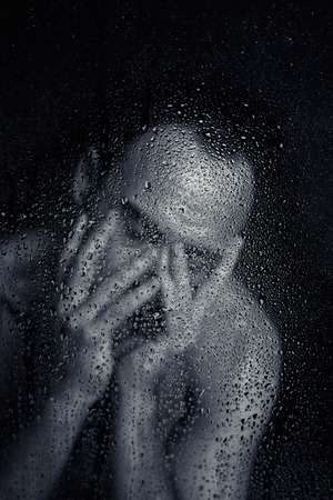 caucasian water drops: Bare man with expressive pose behind wet glass. Stock Photo