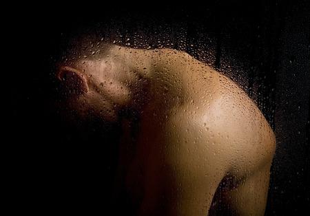 uomo sotto la pioggia: Immagine artistica dell'uomo irriconoscibile dietro vetro bagnato nel buio. Archivio Fotografico
