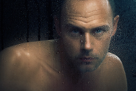 caucasian water drops: Bare man staring in camera behind wet glass.