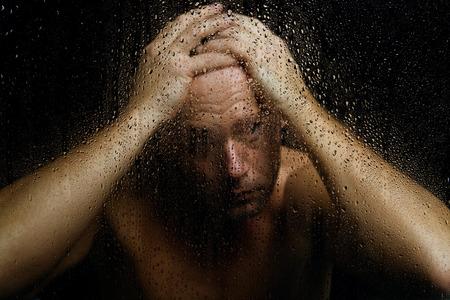 unsecure: Bare man with expressive pose behind wet glass. Stock Photo