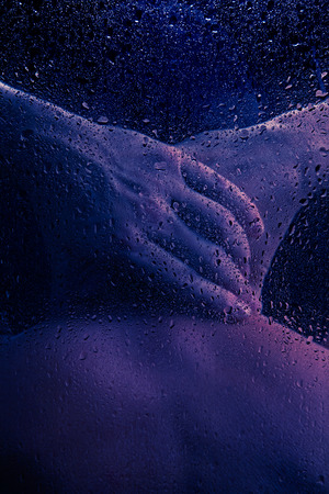 caucasian water drops: Rear view of a man with expressive hands behind wet glass.